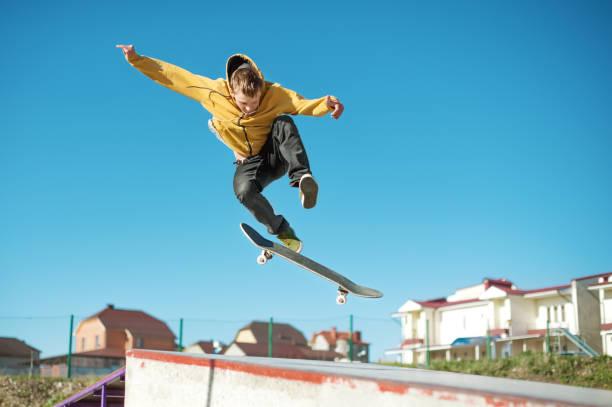 ティーンエイ ジャーのスケートボーダーは都市の郊外にスケートパークでフリップ トリック - スケートボードをする ストックフォトと画像