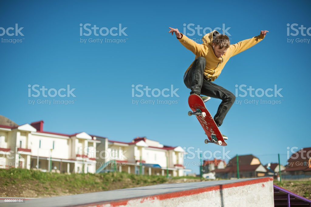 A teenager skateboarder does an ollie trick in a skatepark on the outskirts of the city stock photo