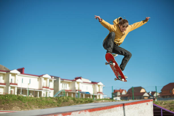 a teenager skateboarder does an ollie trick in a skatepark on the outskirts of the city - skateboard stock pictures, royalty-free photos & images