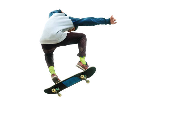 A teenager skateboarder jumps an ollie on an isolated white background. The concept of street sports and urban culture stock photo