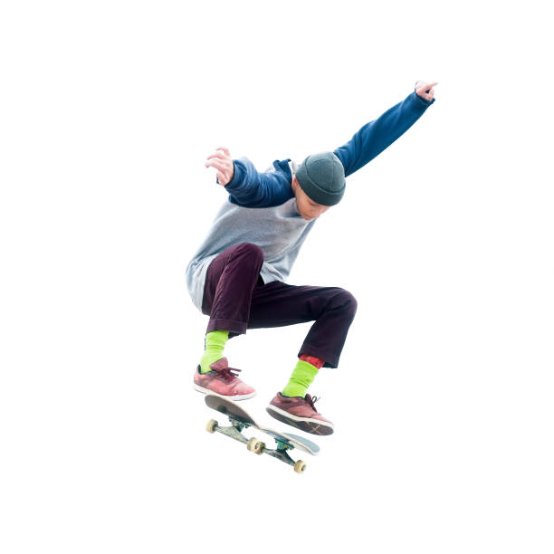 Teenager skateboarder jumps ollie on an isolated white background. stock photo