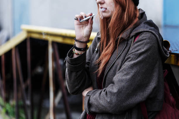 Teenager smoking cigarette Cropped photo of a ginger, teenager smoking a cigarette outside absentee stock pictures, royalty-free photos & images