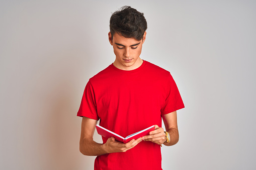 Teenager student boy reading a book over isolated background with a confident expression on smart face thinking serious