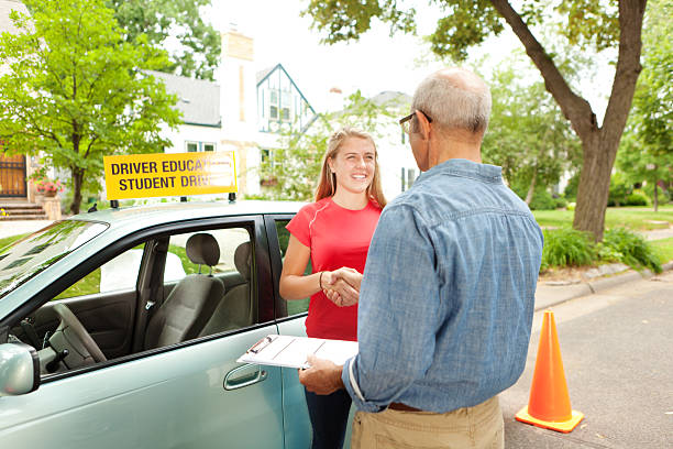 Teenager Student Driver Shaking hand with Driving Instructor Examiner Subject: A young teenager girl passing driving exam with instructor or examiner. driving instructor stock pictures, royalty-free photos & images