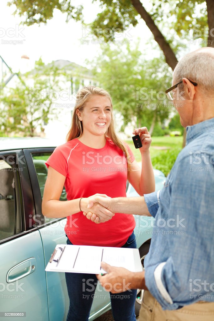 Teenager Student Driver Shaking Hand With Driving Instructor