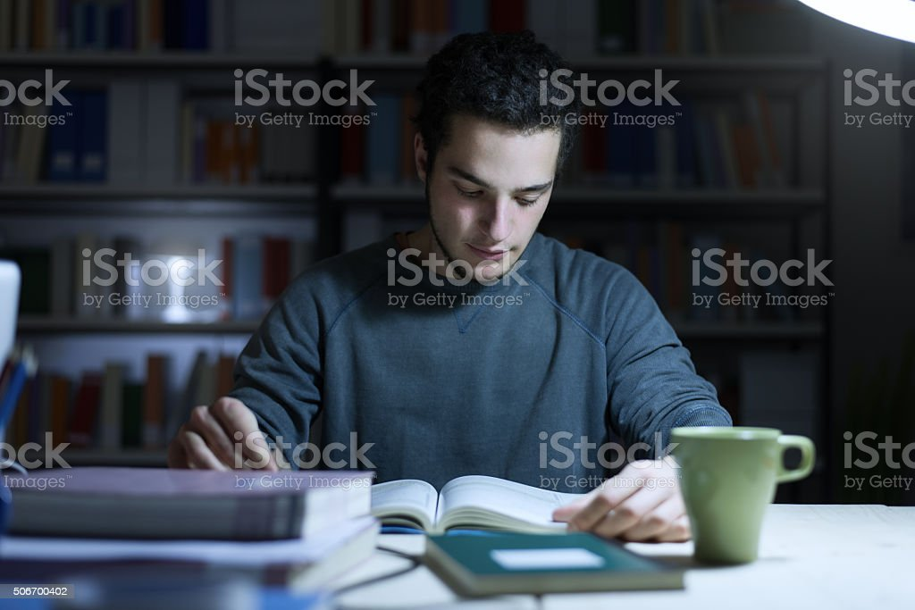 Teenager studying late at night stock photo