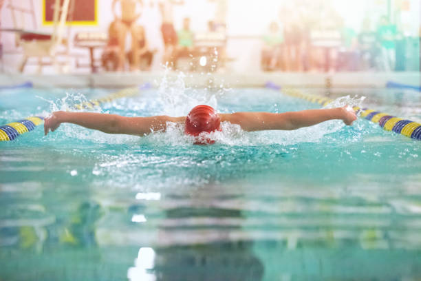 teenager swimming butterfly - competition group stock photos and pictures