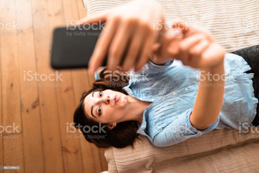 teenager take a selfie on the bed zbiór zdjęć royalty-free