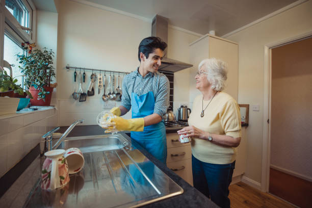 Teenager Talking to Grandmother While Cleaning Teenage boy is talking to his grandmother while he washes the dishes in her kitchen. young at heart stock pictures, royalty-free photos & images