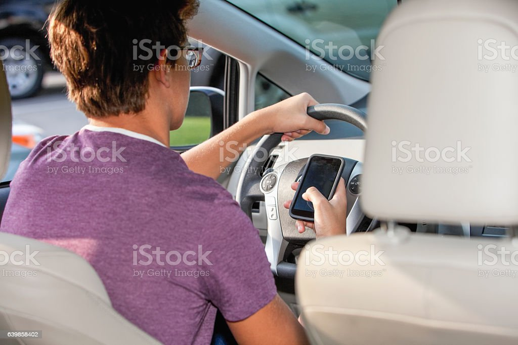 Teenager texting and driving stock photo