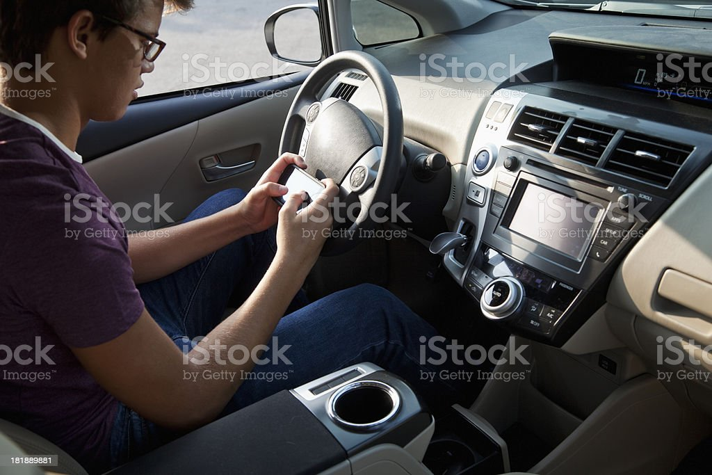 Teenager texting in car stock photo