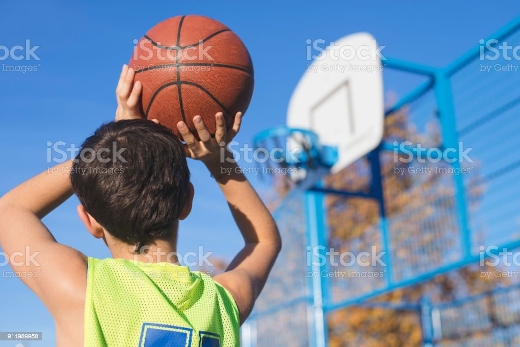 Teenager throwing a basketball into the hoop stock photo