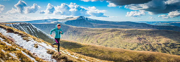 Teenager trail running along mountain path Brecon Beacons panorama Wales Active teenager trail running along rocky path high in the picturesque mountain wilderness of the Brecon Beacons National Park, Wales. ProPhoto RGB profile for maximum color fidelity and gamut. brecon beacons stock pictures, royalty-free photos & images