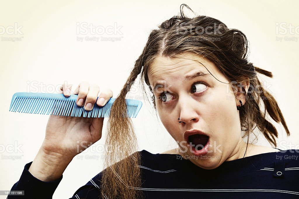 Teenager tries to comb tangled hair with no success royalty-free stock photo