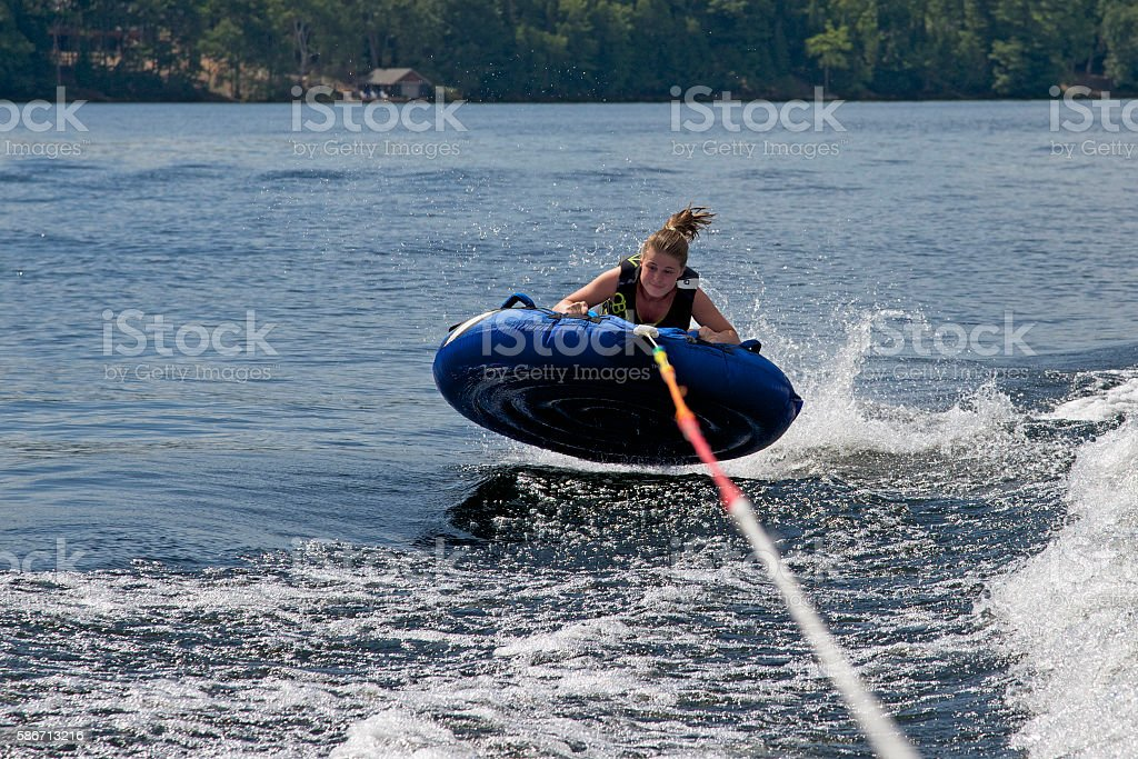 Teenager tubing behind a boat on Lake of Bays stock photo