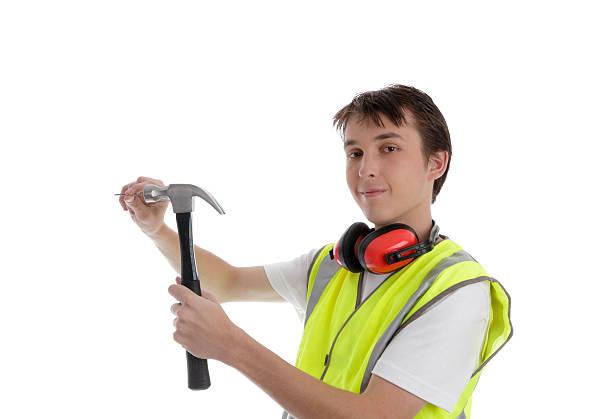 Teenager using a hammer and nail stock photo