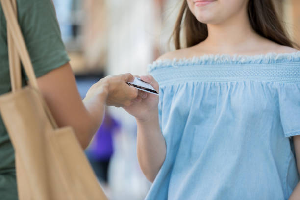 Teenager using mom's credit card while shopping Unrecognizable woman is giving a credit card to a Caucasian teenage girl  at an outdoor mall. Women are wearing casual clothing. allowance stock pictures, royalty-free photos & images