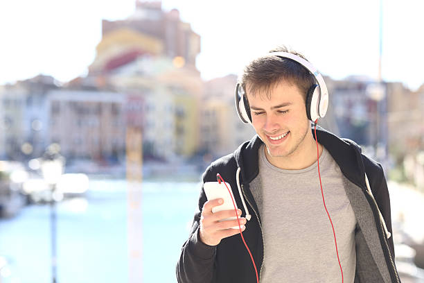 teenager walking listening music from smart phone - geräusche app stock-fotos und bilder