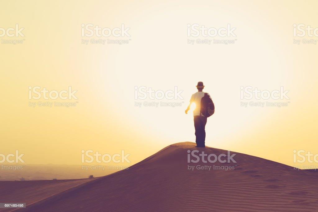 Teenager walking towards the rising sun on the Arabian dunes