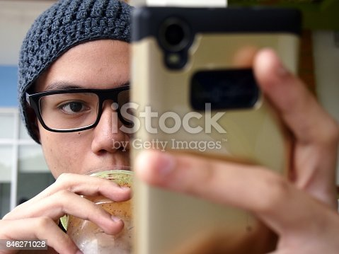 Photo of a teenager wearing a bonnet and eyeglasses using a smartphone