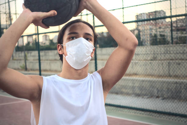 Teenager wearing a mask in basketball court getting ready to shoot the ball stock photo