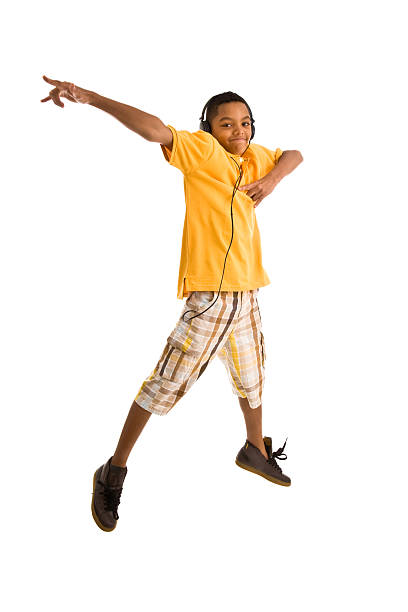 teenager wearing headset and jumping arms outstretched - african youth jumping for joy stock photos and pictures