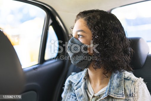 Teenager wearing N95 face mask on car trip during the coronavirus pandemic in 2020