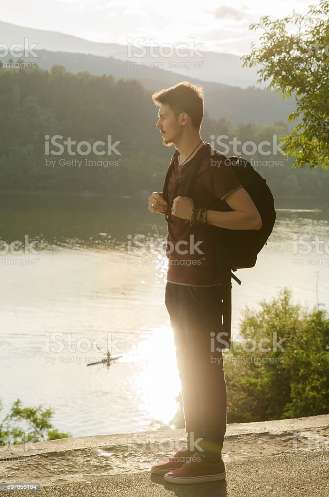 Teenager with backpack on a lake stock photo