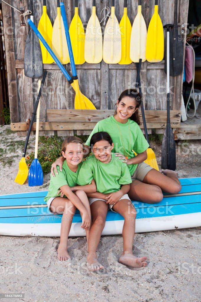 Adolescent avec filles assis sur paddle - Photo