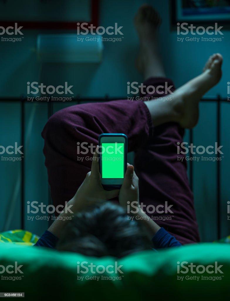 Teenager mit Greenscreen im Bett – Foto