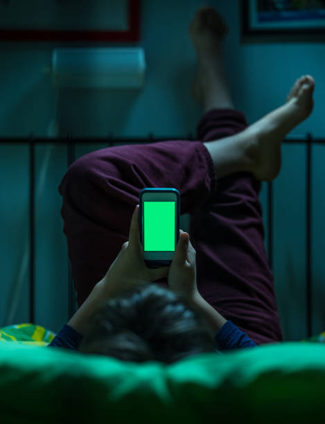 teenager with green screen in bed - smartphone addiction not groups stock pictures, royalty-free photos & images