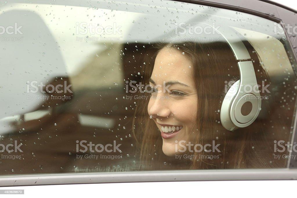 Adolescente con auriculares escuchando la música en un coche - foto de stock