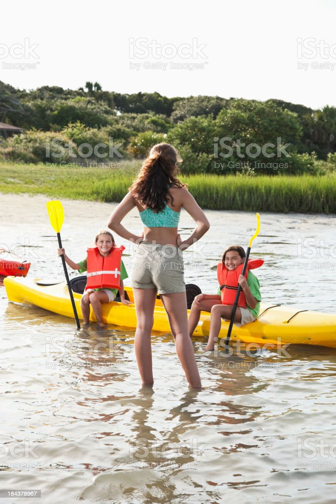 Teenager with little girls sitting on kayak royalty-free stock photo