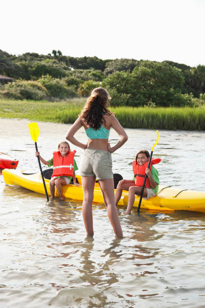 Teenager with little girls sitting on kayak Teenage girl (17 years) helping young kayakers (8-9 years).  Main focus on teenager. akimbo stock pictures, royalty-free photos & images