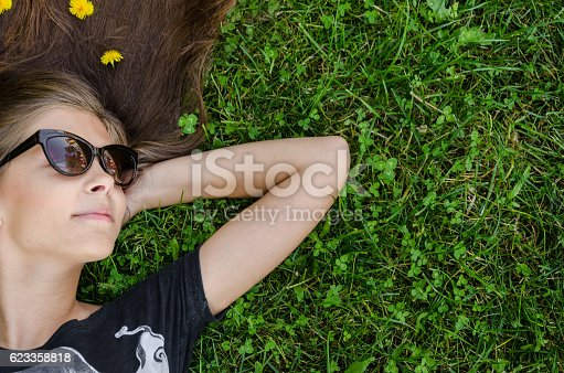 istock teenager with stylish sunglasses lying on green grass 623358818