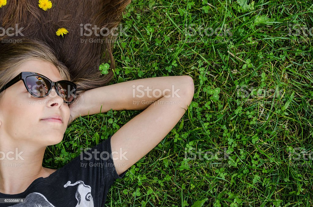 teenager with stylish sunglasses lying on green grass stock photo
