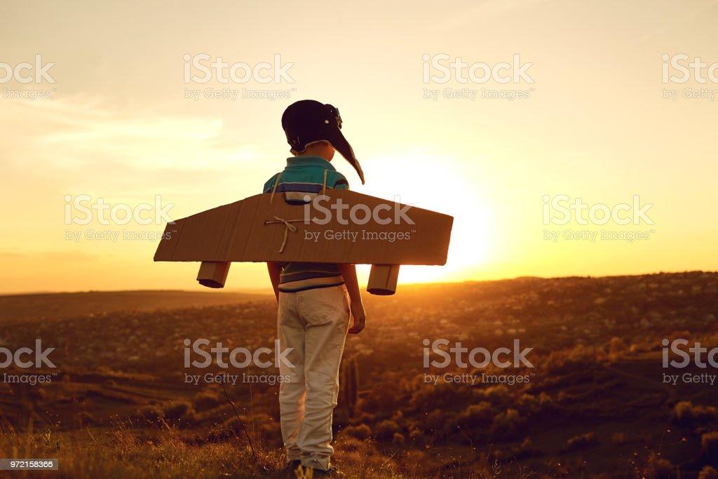 Adolescente con avión de juguete en naturaleza al atardecer - foto de stock