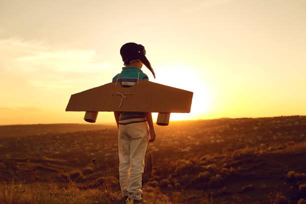 Teenager mit Spielzeugflugzeug über Natur bei Sonnenuntergang – Foto