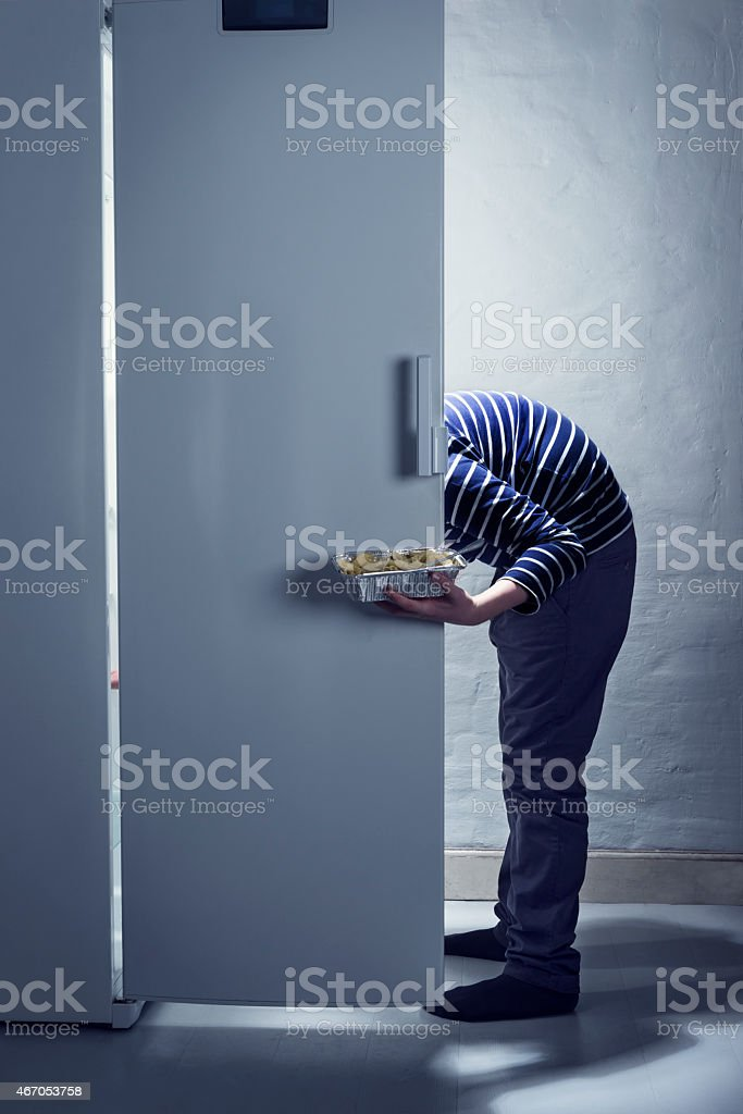 TeenagerCaught Getting a Midnight Snack From The Fridge stock photo