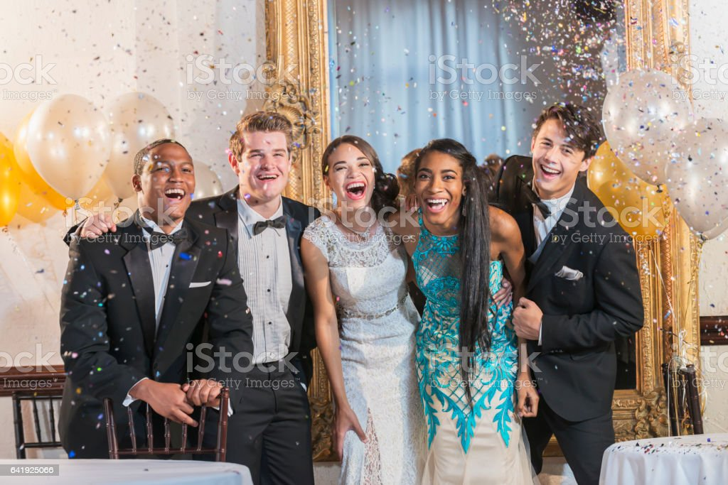 Teenagers and young adults in formalwear at party stock photo