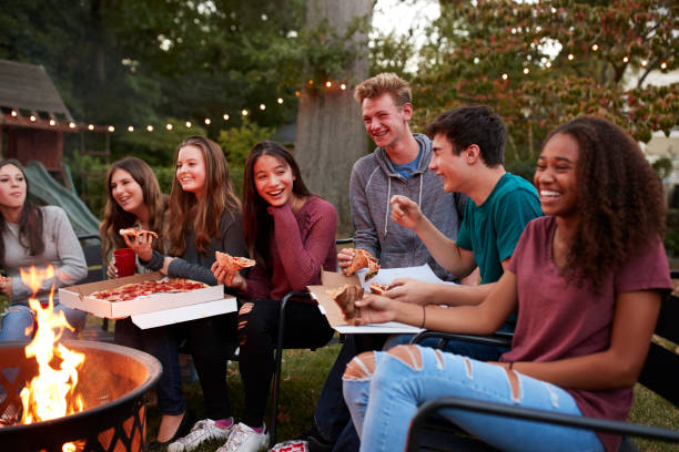 Teenagers at a fire pit eating take-away pizzas, close up stock photo
