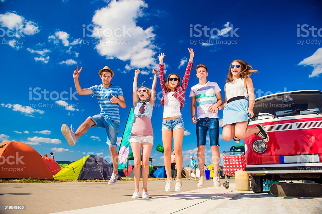 Teenagers at summer festival jumping by vintage red campervan stock photo