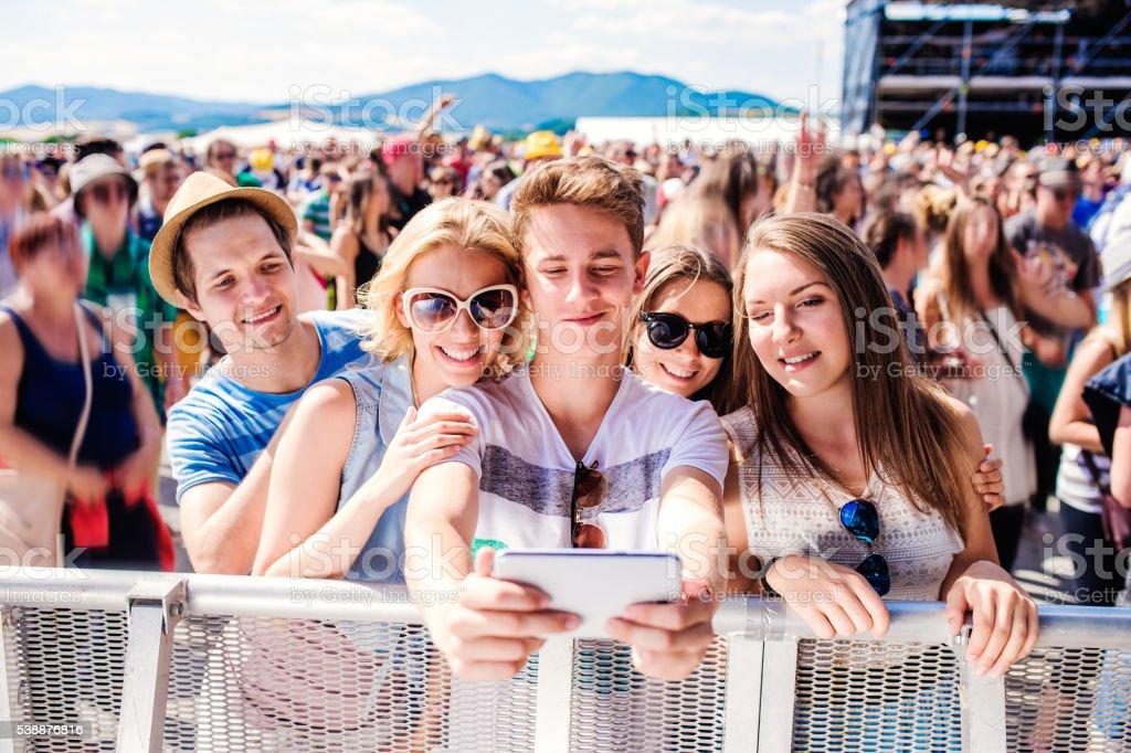 Adolescentes no Festival musical de verão em público e tirando selfie - foto de acervo