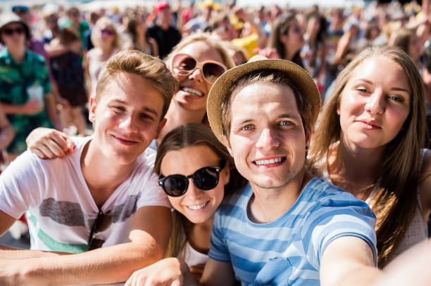 Teenagers at summer music festival in crowd taking selfie stock photo