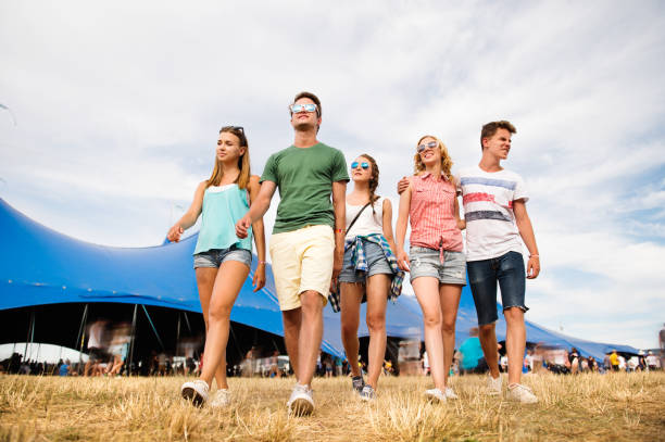 teenagers at summer music festival in front of big blue tent - tanz shorts stock-fotos und bilder