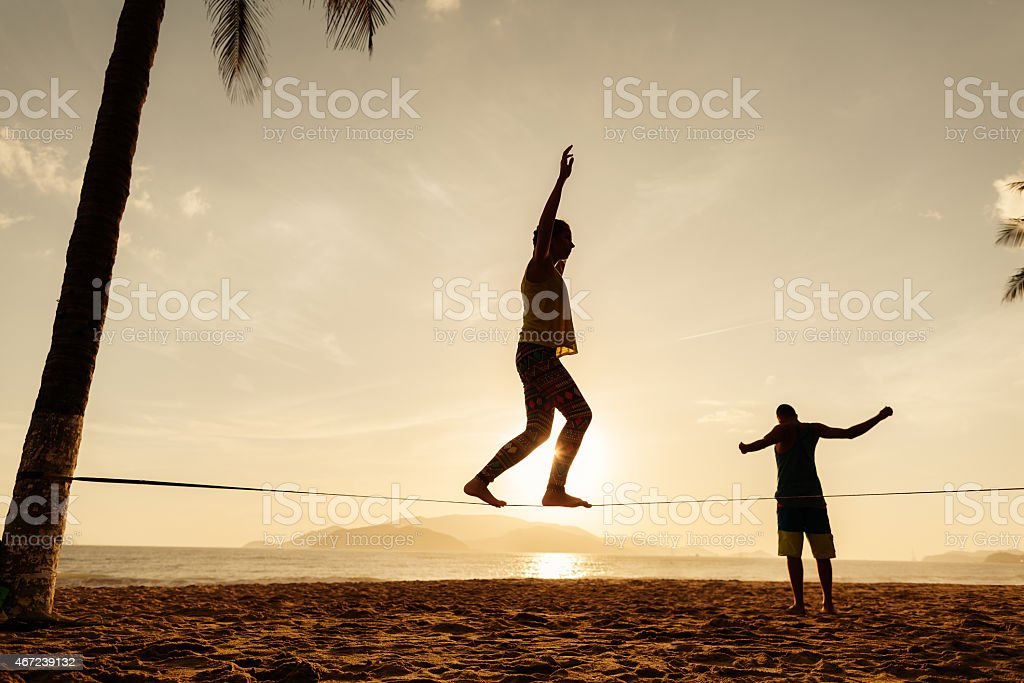 teenagers balance on slackline silhouette stock photo