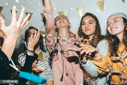 Photo of a smiling teenage girls having fun while celebrating New Year's Eve and tossing confetti in the air