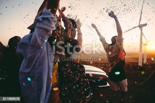 Group of multi-ethnic teens dressed in boho style partying outdoors throwing colourful confetti in a wind farm at sunset during their american carefree road trip
