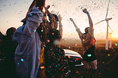 Teenagers celebrating with colourful confetti on summer road tri