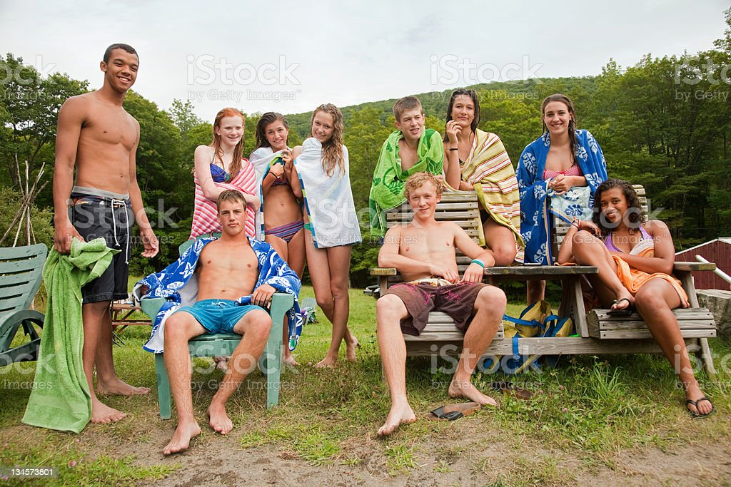 Teenagers chilling out together in swimming clothes in countryside stock photo